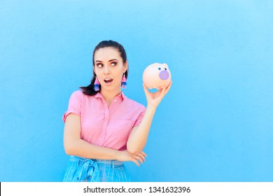 Woman Checking her Financial Status Shaking Piggy Bank. Smart millennial thinking about saving money and paying all debt