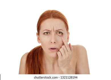 Woman checking her health condition looking into her eye, closeup portrait isolated on white background. Yellowish eyes is sign of problems with liver, viral infection or other disease