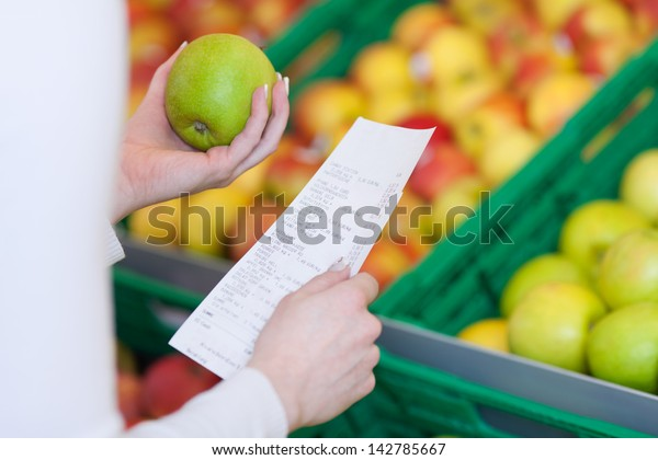 Woman checking her till slip or receipt when shopping for fresh fruit in a supermarket holding a green apple in her hand