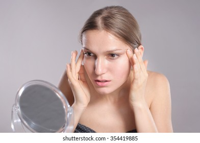 Woman checking her wrinkles on her face
