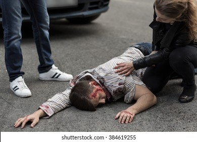 Woman checking if man hit by a car is alive