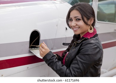 A woman is checking the oil in an airplane.