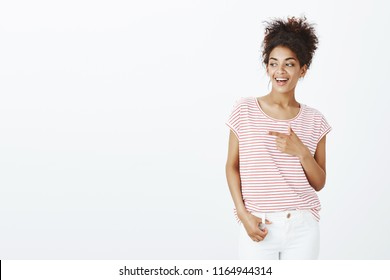 Woman checking out hot guy. Positive beautiful female student with combed curly hair in striped t-shirt, pointing and looking left with satisfied happy expression, seeing something intriguing
