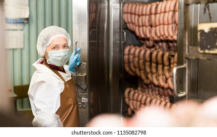 Woman checking quality of cooked smoked sausages in professional baking machine at food production factory
