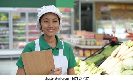 The woman is checking the quality of the products in the fruit and vegetable department.