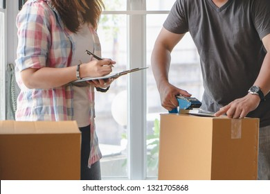 woman checking stuff in cardboard box before sent to transportation company and moving to new location apartment.