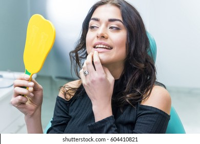 Woman checking teeth in mirror. Female at the dentist office.