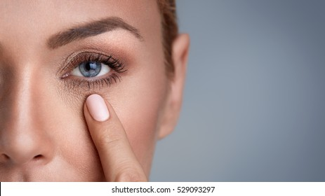 woman checking wrinkles around the eyes, close up