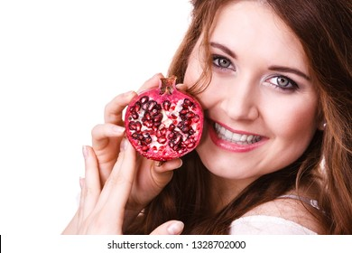 Woman cheerful brunette girl holding pomegranate fruits in hands, isolated on white. Healthy eating, cancer prevention, immune support.