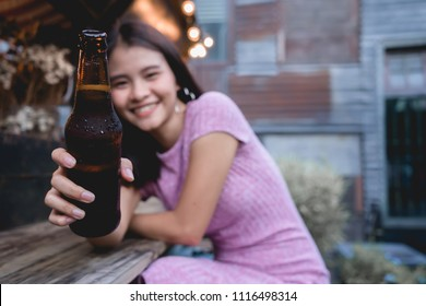 Woman cheers drinking beer bottle. Young girl clinking toast alcohol in bar. Lady people party in club having fun. Asian female give beer bottle to you.