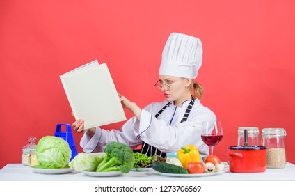 Woman chef cooking healthy food. Girl read book top best culinary recipes. Culinary school concept. Female in hat and apron knows everything about culinary arts. Traditional cuisine. Culinary expert.