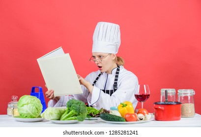 Woman chef cooking healthy food. Girl read book best culinary recipes. Culinary education concept. Female in hat and apron knows everything about culinary arts. Improve cooking skill. Culinary expert.