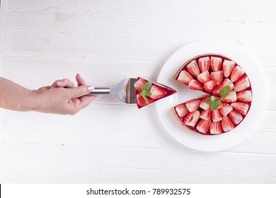 Woman chef hand holding a slice of organic healthy vegetarian no bake strawberry cheesecake, red berries, green mint leaves, cake spoon. Ceramic plate on white wooden table background. copy space top
