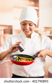 Woman chef holding red skillet with chopped vegetables inside, adding salt from metal container