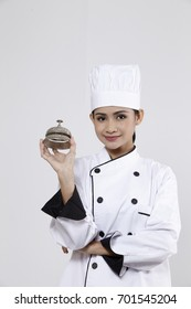 woman chef holding a silver service bell