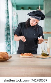 woman chef seasoning a dish of galician octopus, spanish recipe at a Kitchen