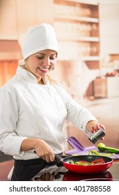Woman chef smiling using red skillet frying vegetables and adding salt