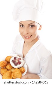 Woman chef in uniform holding tray of cookies.