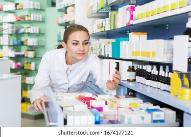 Woman chemist is searching medicine in drawers in apothecary.