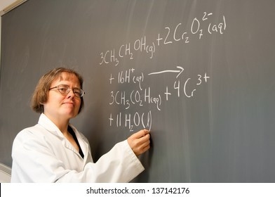 """A woman chemistry instructor writes out a chemical equation on a chalk board. The equation describes the chemistry behind the """"breathalyzer"""" test."""