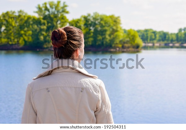 A woman with a chignon looking at the river during a nice sunny spring morning