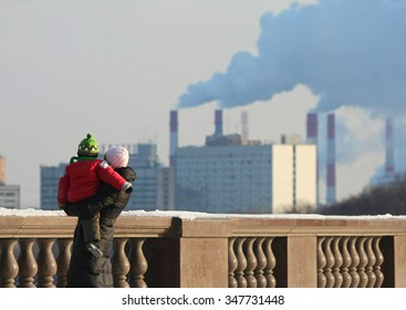 Woman with the child against pipes with a smoke