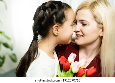 Woman and child with bouquet of flowers against home background. Spring family holiday concept. Women's day