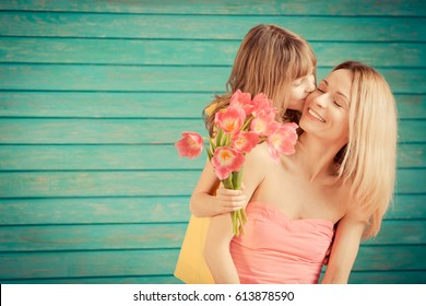 Woman and child with bouquet of flowers against green background. Spring family holiday concept. Mother's day