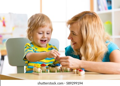 Woman and child boy talking and smiling while playing with educational toys together in daycare centre