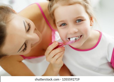 Woman and child brush their teeth