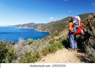 Woman with child carrier on back admiring the view in Cinque Terre, Italy