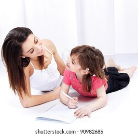 Woman and child drawing on notepad and laughing