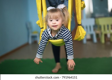 woman with child engaged in air yoga, yellow hammock, concept childhood and lifestyles