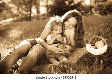 Woman and child having picnic in park - monochrome photo in retro style, sepia toned