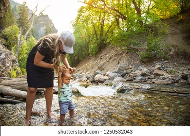 Woman and child hiking across a beautiful scenic mountain river. Walking in the mountain stream on a warm summer day together. lifestyle photo of a mother and her son in the outdoors