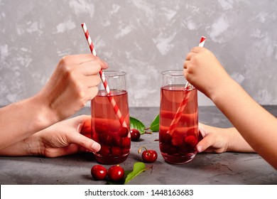 Woman and child holding in hands fresh cherry lemonade with paper straw in glasses on gray background, copy space. Cold summer drink. Sparkling glasses with berry cocktail