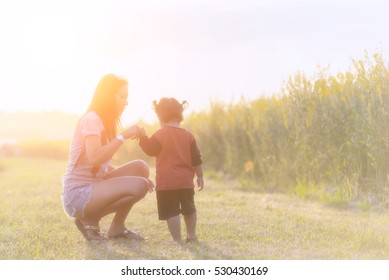 The woman and child holding hands at sunset