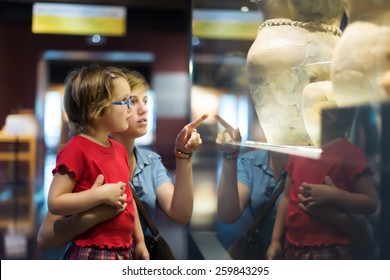 Woman and child looking old ancient amphora in historical museum