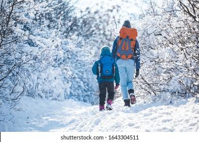 Frau mit Kind auf einer Winterwanderung in den Bergen. Der Junge reist in der kalten Jahreszeit mit Mutter. Ein Kind mit Rucksack geht mit Mutter in einem schneebedeckten Park spazieren. Trekking mit Kindern. Winterausflug.