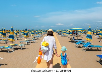 Woman and child outdoors. Mother and daughter going to rest on beach. Rimini, Italy.