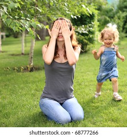 Woman and child playing hide and seek in summer park