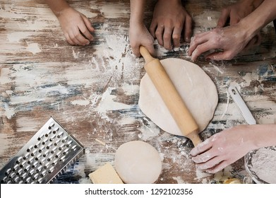 Woman with child preparing dough for homemade pizza. Light toning. Top view