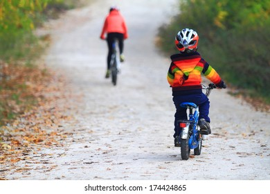 Woman and child racing bikes on autumn road