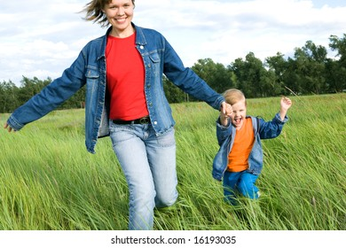 woman and child run on field. happy family