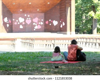 woman and child sitting in a sofia park in front of theater scene decorated with shape of heart