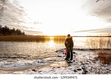 Woman and child standing on a cold frozen beach with snow. Beautiful gold winter landscape sunset over calm water against the sea horizon with bright sun.