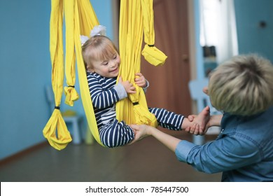 woman and child Toddler with Down syndrome air yoga, yellow hammock. Lifestyle and tinting, compensatory classes in the center