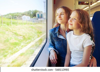 Woman with child traveling by public transport. Family traveling in a train and looking through the window