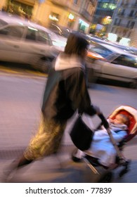 Woman with child walking on the sidewalk in a very busy city