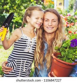 Woman and child working at garden. Female gardener outdoors. Gardening